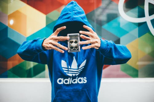 Man in Blue Adidas Hoodie Doing Magic Trick