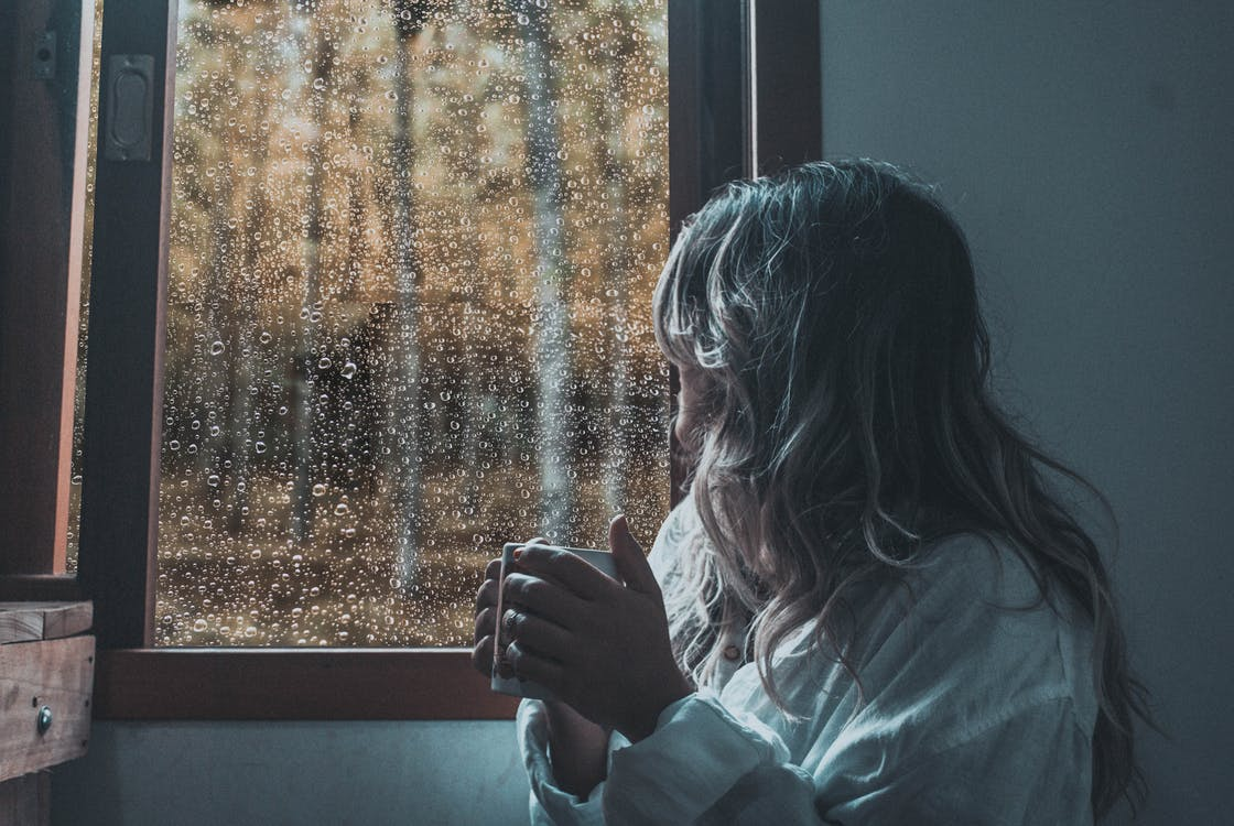 Woman in White Long Sleeve Shirt Looking at Glass Window