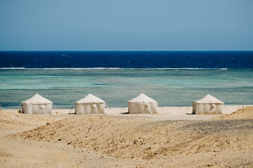 Beach tents placed on sandy seacoast in tropical resort camp