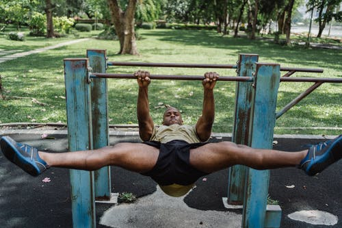 Man with Open Legs Lifting His Body on Pull Up Bars