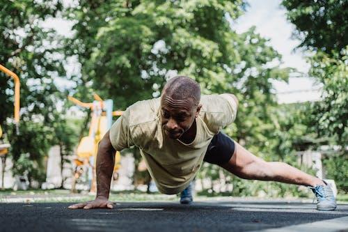 Man Doing One Arm Push UPs on Pavement