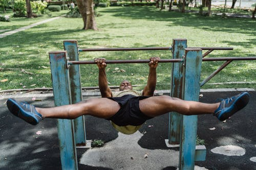 Man with Open Legs Pulling Up His Weight on a Bar