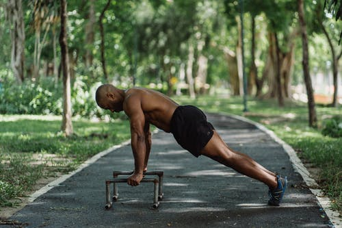 Topless Man Doing Push Up on Low Dip Bars