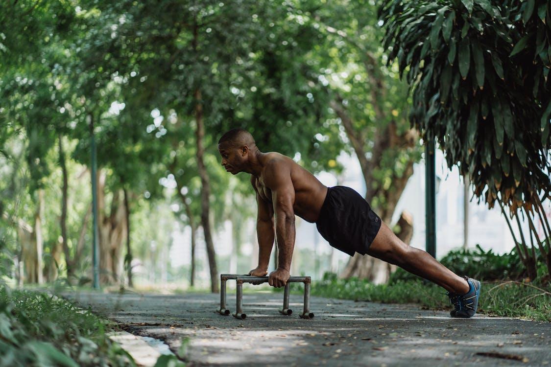 Shirtless Man Doing Push Ups Using Low Dip Bars at the Park