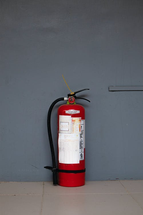 Red Fire Extinguisher Against Wall