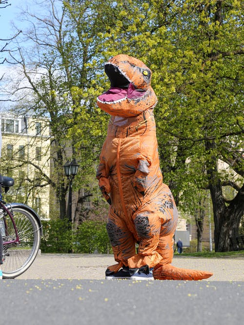 Faceless person in dinosaur costume standing on city street
