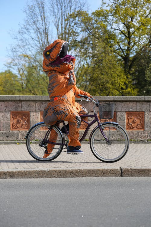 Unrecognizable performer in costume of dinosaur riding bicycle