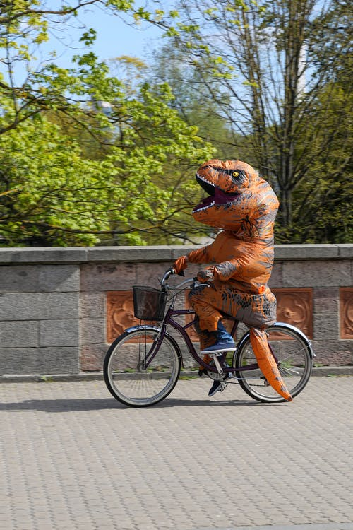 Amusing faceless person in dinosaur costume cycling on sidewalk