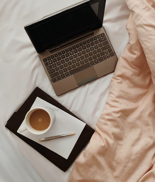 Laptop near notebook and cup of coffee on bed