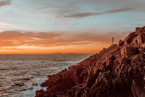 Amazing scenery of lighthouse in distance located near rocky coast with waving ocean with sun setting on horizon in summer evening