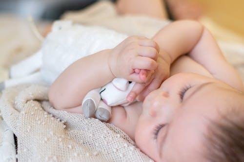 Baby Lying on White Textile