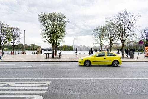 Yellow Sedan on Gray Asphalt Road