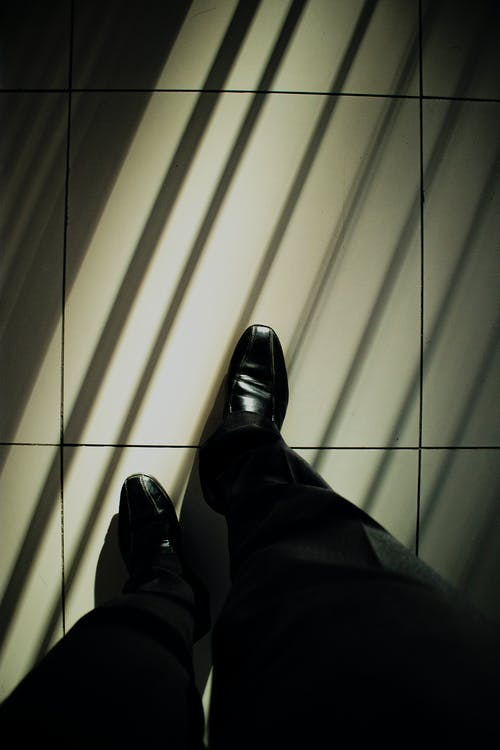 Person in Black Pants and Black Leather Shoes