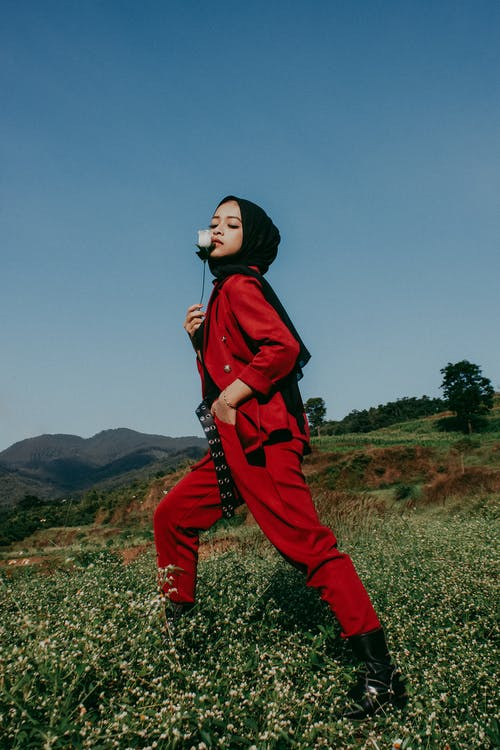 Woman in Red Coat and Pants Standing on Green Grass Field