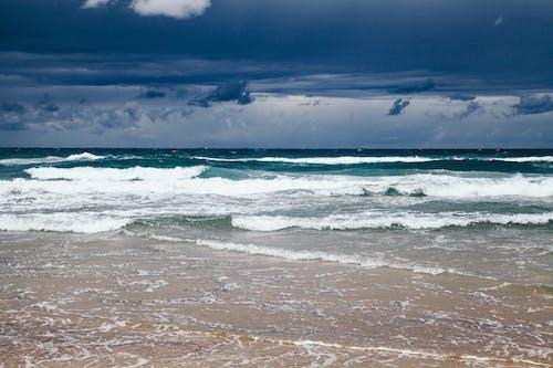 Ocean Waves Crashing on Shore Under Dark Clouds