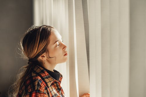 Pensive young woman looking out window on sunny day