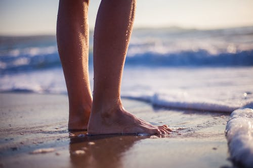 Person Standing Barefooted on Seashore