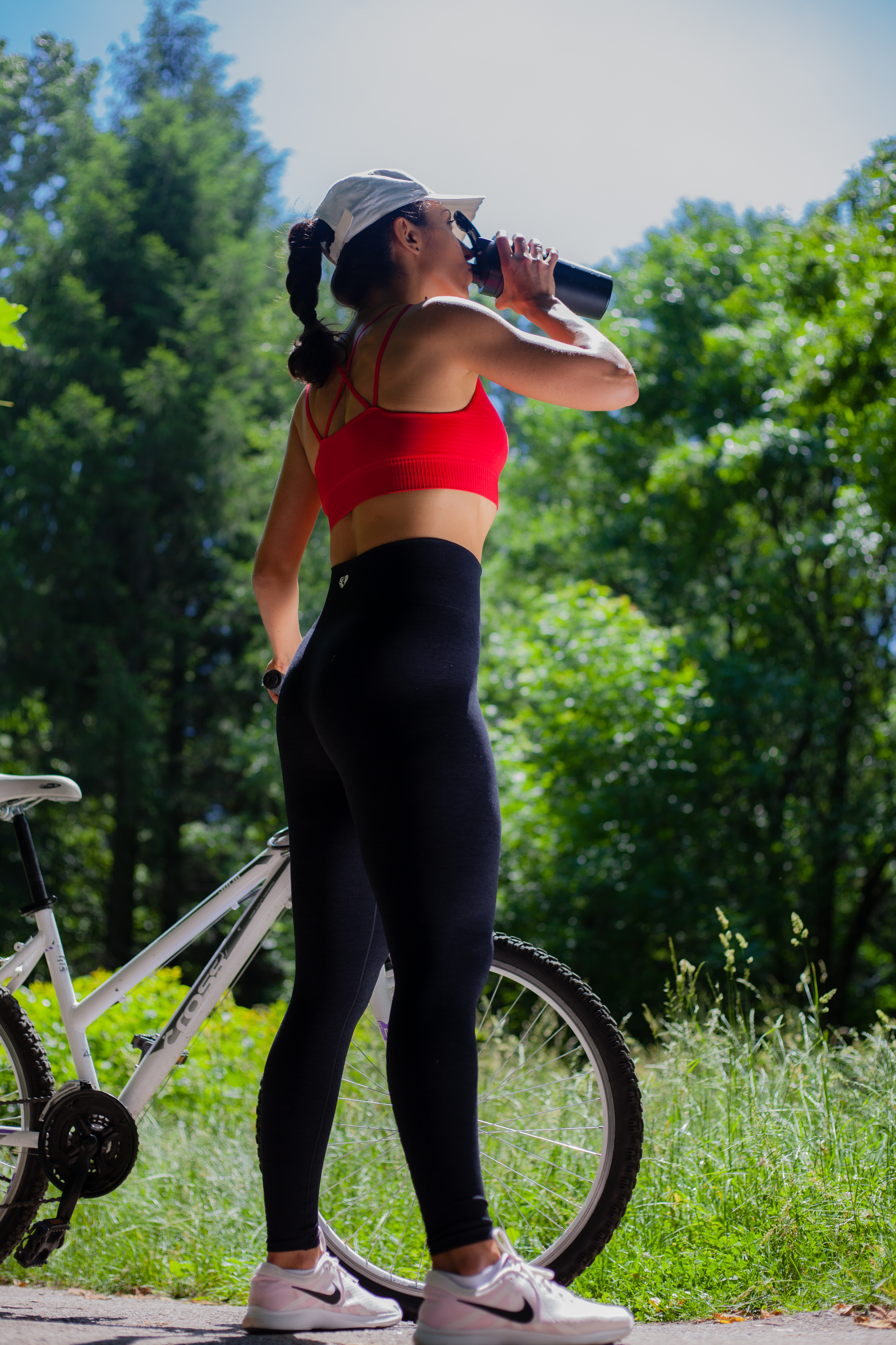 woman in activewear drinking in a black tumbler