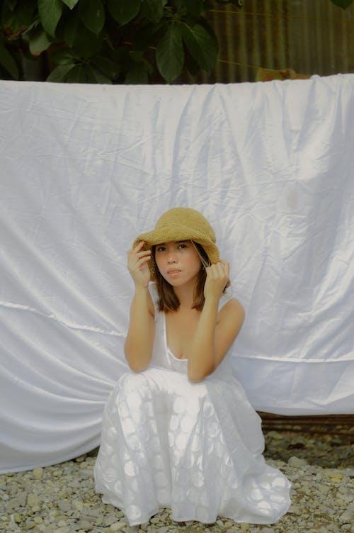 Woman in White Dress Wearing Brown Sun Hat