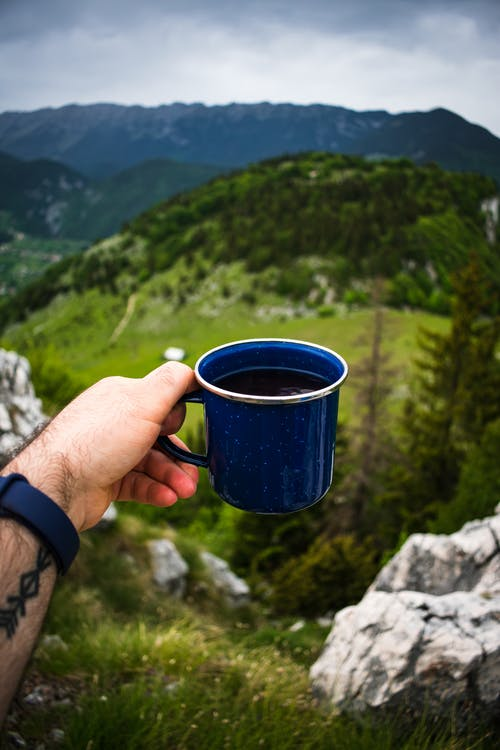Person Holding Blue Ceramic Mug
