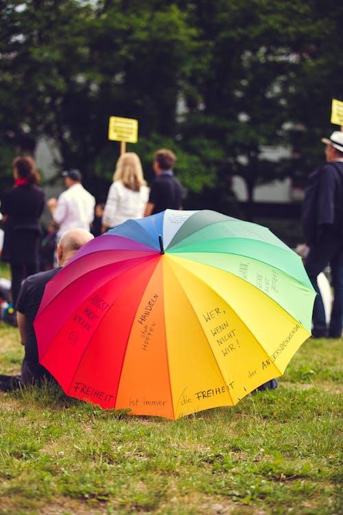People Holding Yellow Umbrella