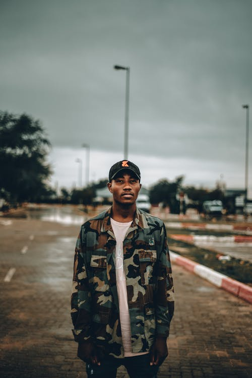 Serious black male in camouflage jacket and cap standing at empty parking against road with cars and cloudy sky