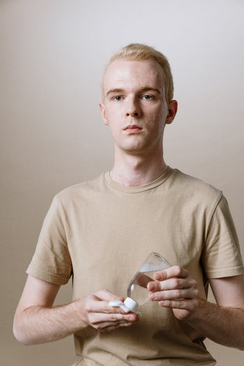 Man in Beige Crew Neck T-shirt Holding Clear Drinking Glass