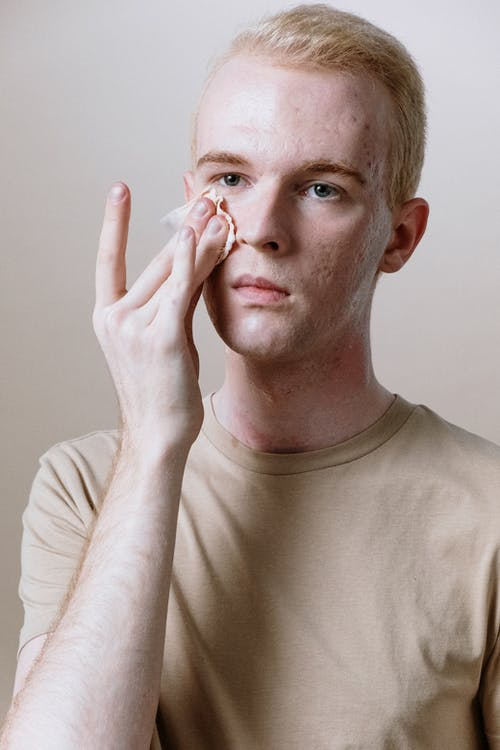 Man in Beige Crew Neck Shirt Covering His Face