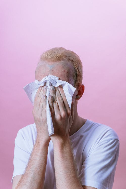 Man in White Crew Neck T-shirt Covering His Face With White Textile