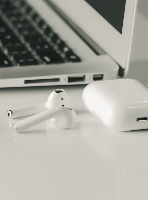Apple Airpods Beside A Macbook Pro