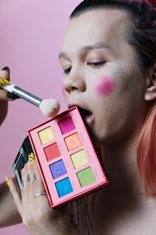 Woman With Pink Lipstick Holding Pink Eyeshadow Palette