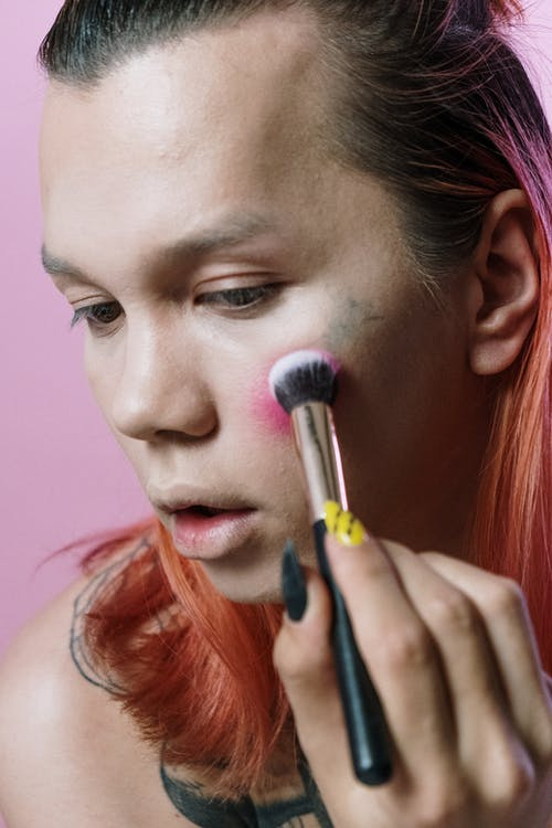 Woman With Pink Hair Holding a Makeup Brush