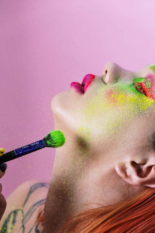 Person With Green and Pink Powder on Face