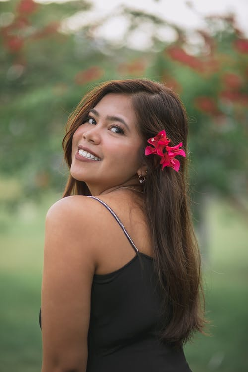 Side view attractive content ethnic female decorating long hair with red flower and looking at camera over shoulder while standing in lush garden