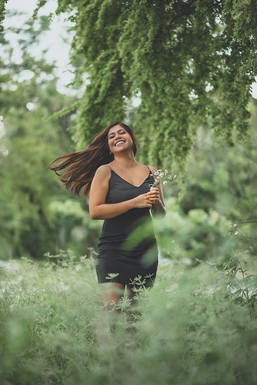 Excited ethnic woman with flowers standing in lush nature