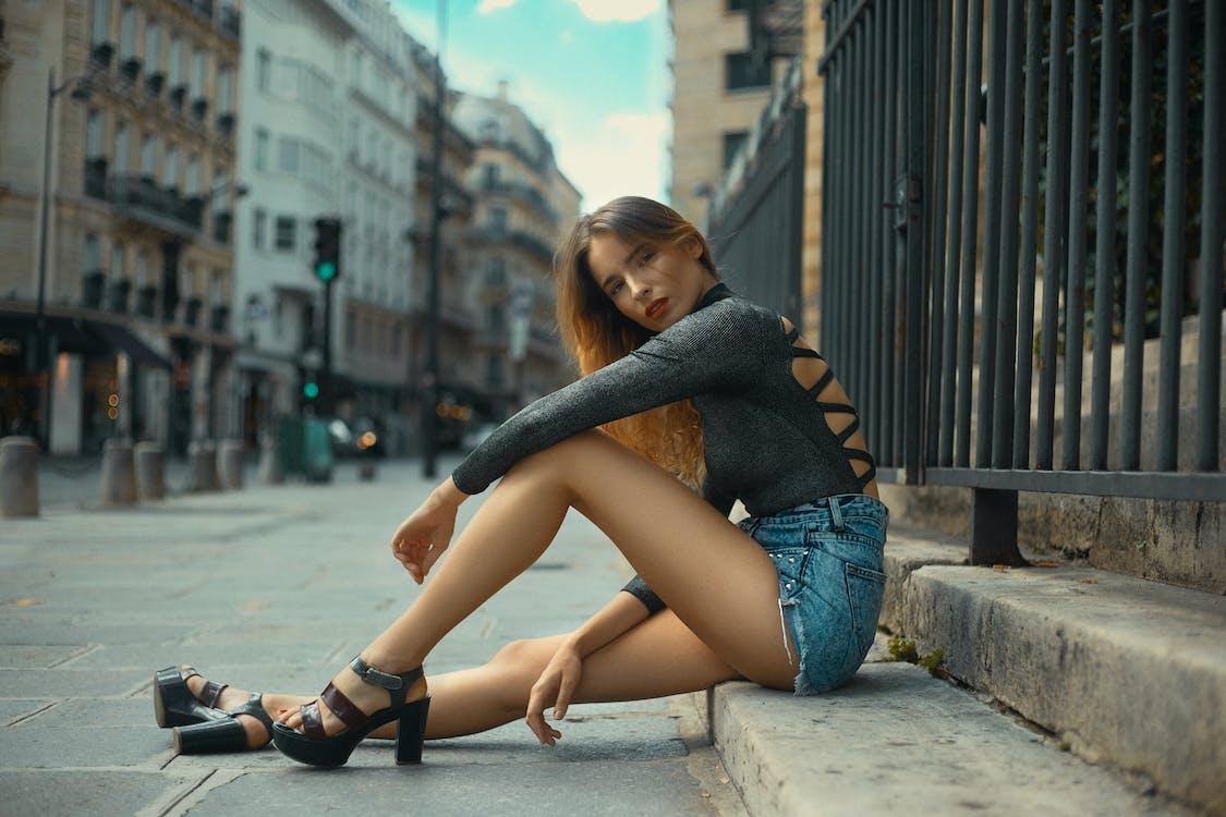 Gorgeous Woman Sitting on Concrete Gutter