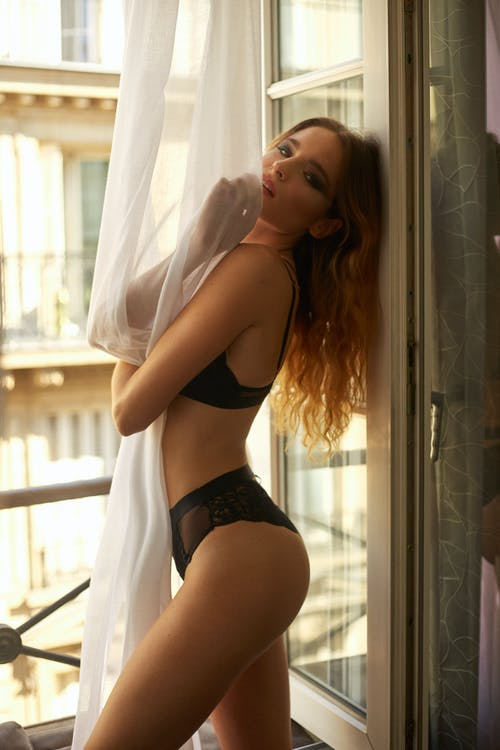 Side view of sensual slim young female in sexy lingerie covering body with curtains while standing near window in bedroom