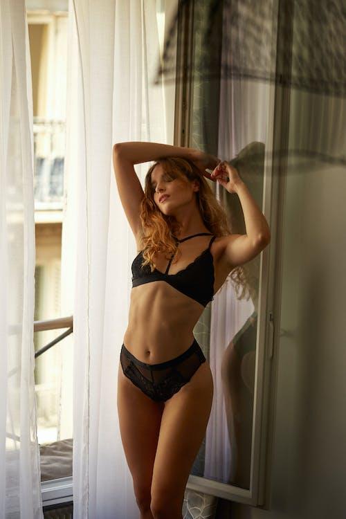 Slim sensual female in underway standing near window in morning