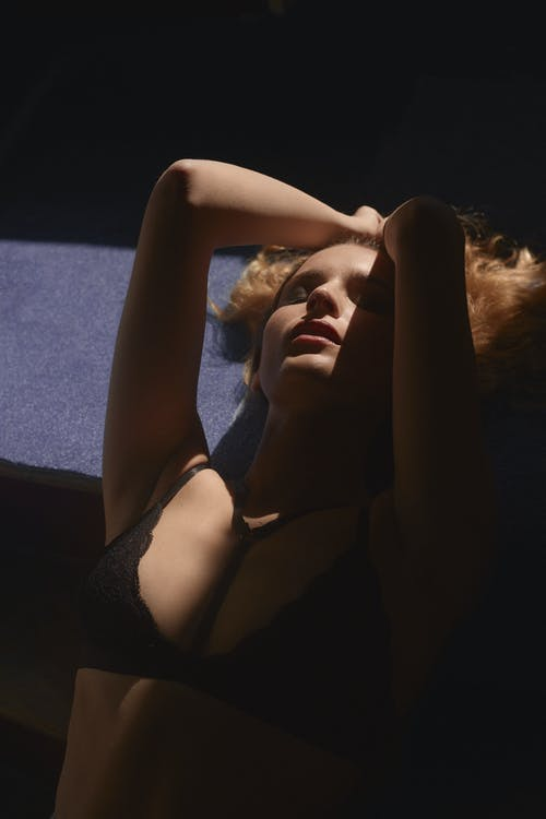 Sexy young lady lying on floor in dark room