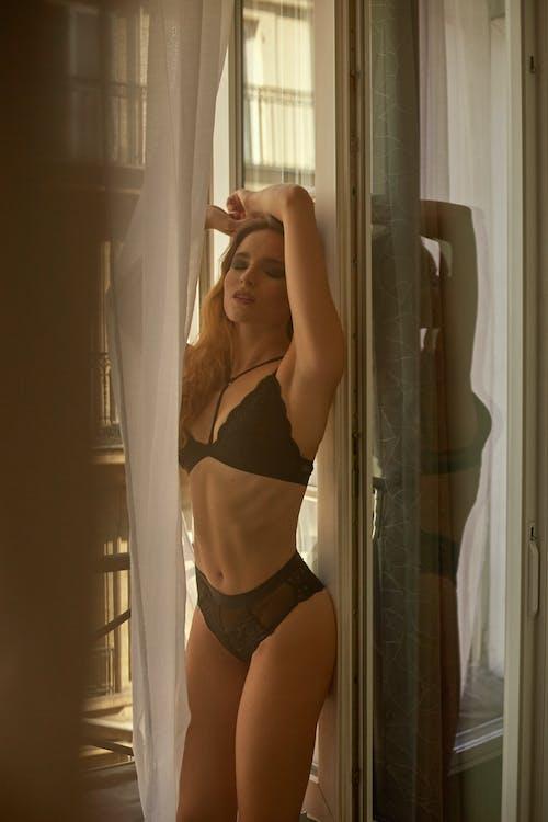Graceful young slim woman relaxing near balcony in bedroom