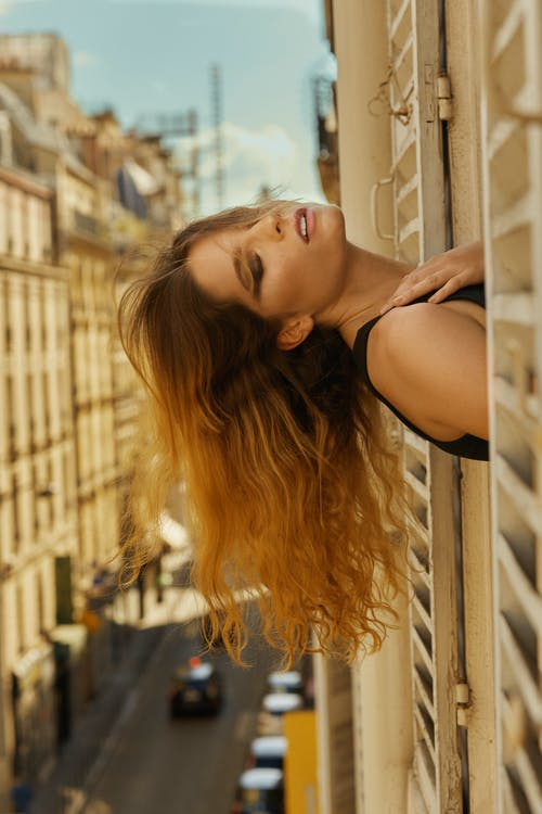 Calm young woman with closed eyes sticking head out of window