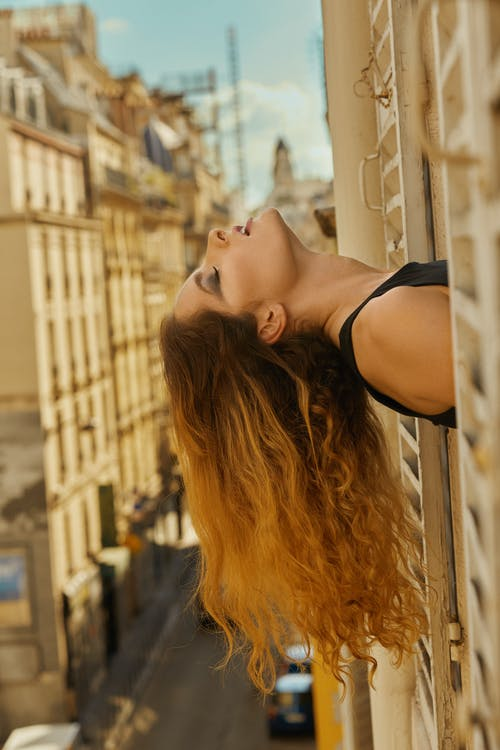 Pensive young lady leaning out of window with closed eyes