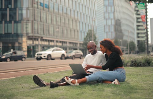 Man and Woman Sitting on Green Grass Field Using Macbook