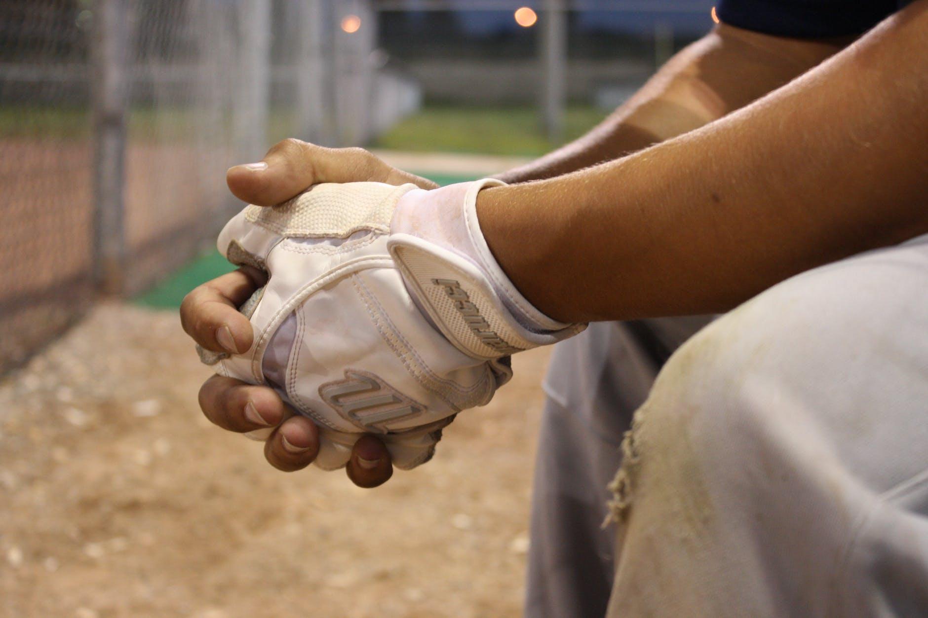Baseball player sitting near fence