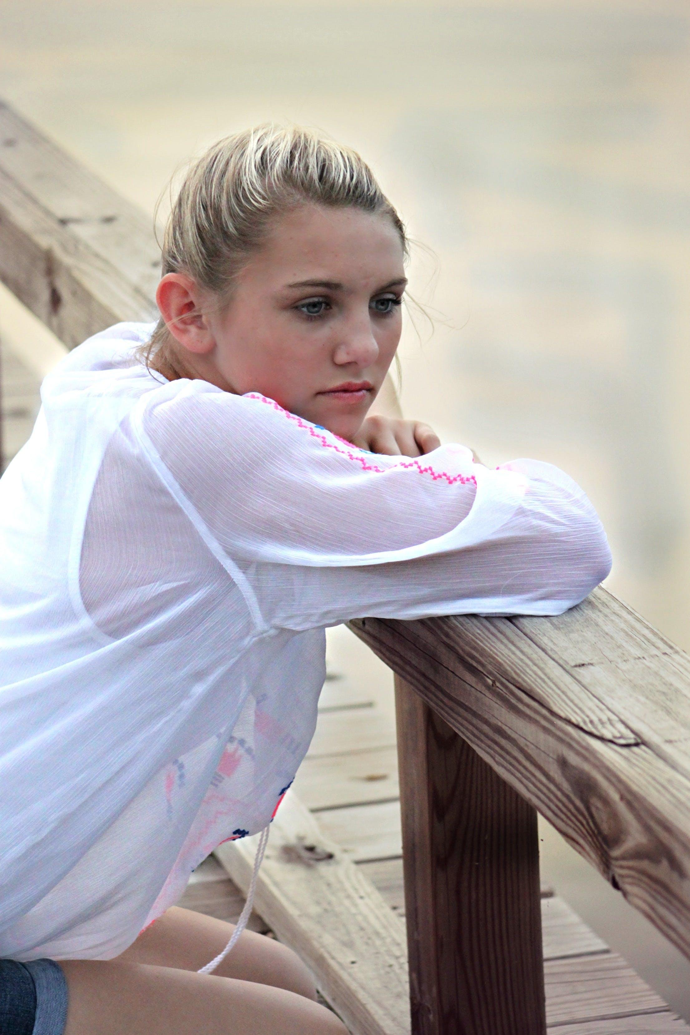 Woman on White Sweatshirt Leaning on Brown Wooden Bridge Frame