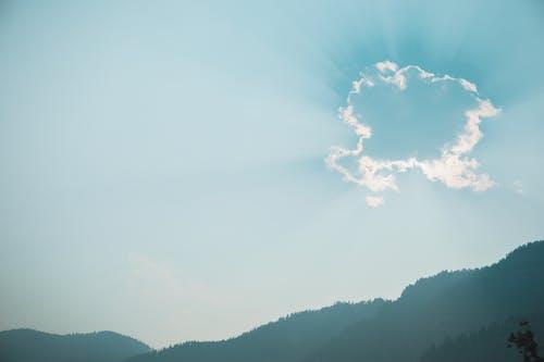 Sun shining through cloud over mountains