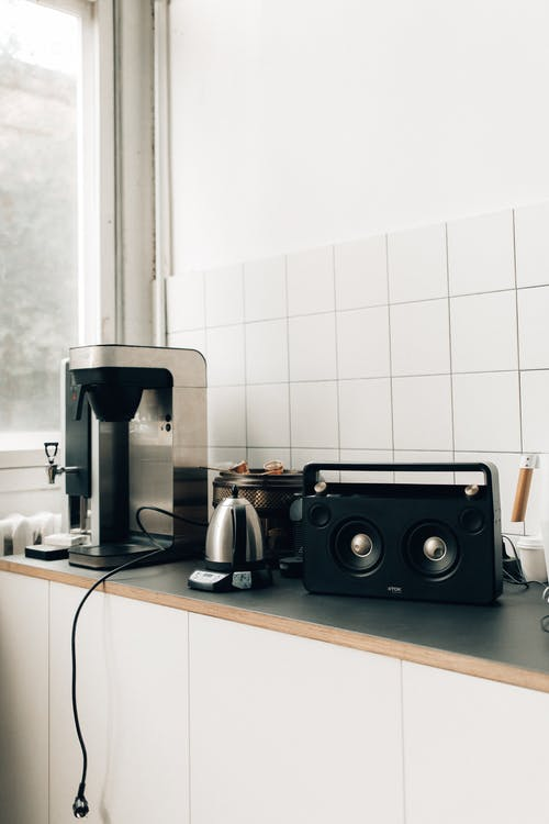 Black and Silver Coffee Maker Beside White Ceramic Wall Tiles