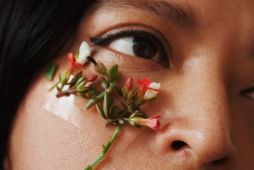 Woman With Red and White Flower on Her Face