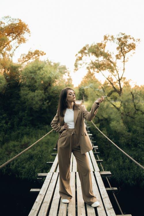 Woman in Beige Long Sleeve Dress Standing on Hanging Bridge