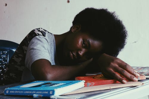 Tired black woman lying on table with books